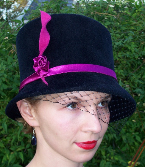 Assymetrical black top hat with pink rose detail and veil